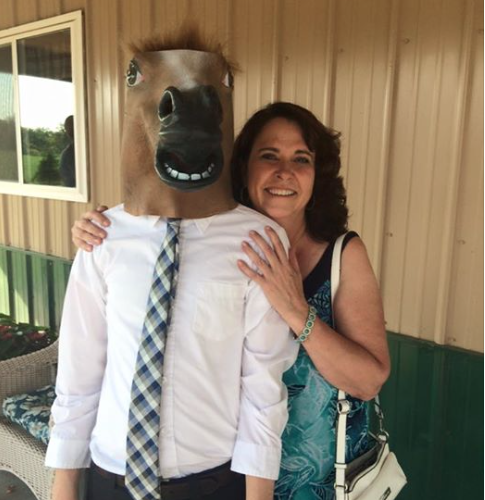 Woman standing next to a man with a rubber horse head on.